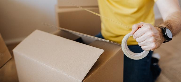 Man sealing a carton box