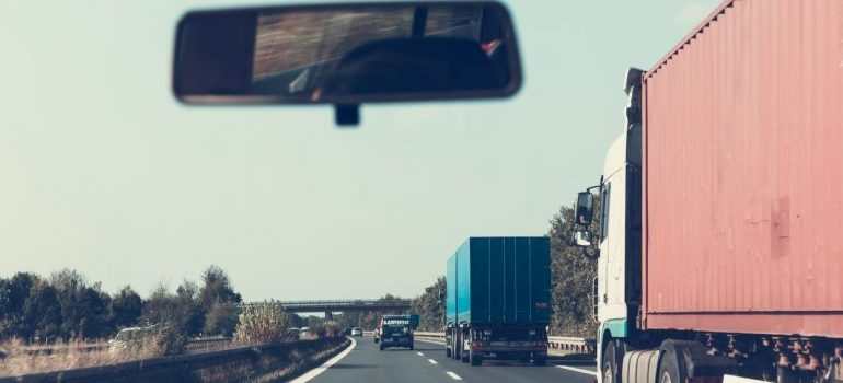Trucks on a highway seen from inside a car.