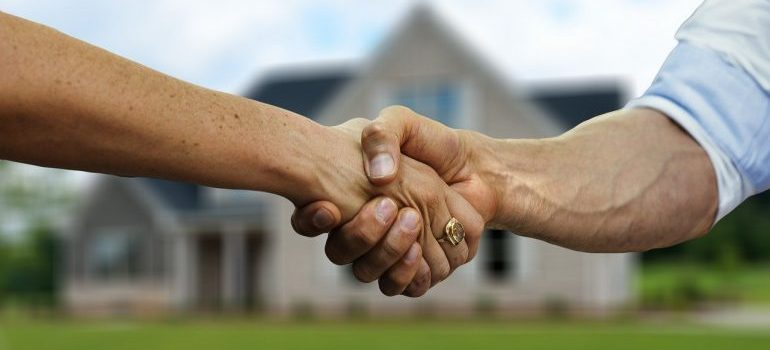 A handshake of two people in front of a house.