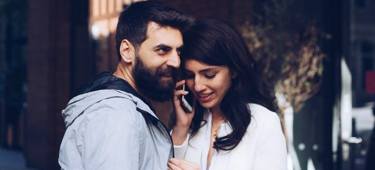 A man and a woman making a phone call.