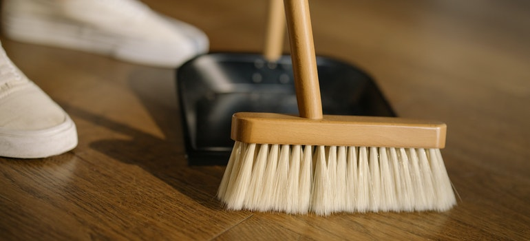 Person using a wooden brush to clean the floor and keep the storage unit clean and neat