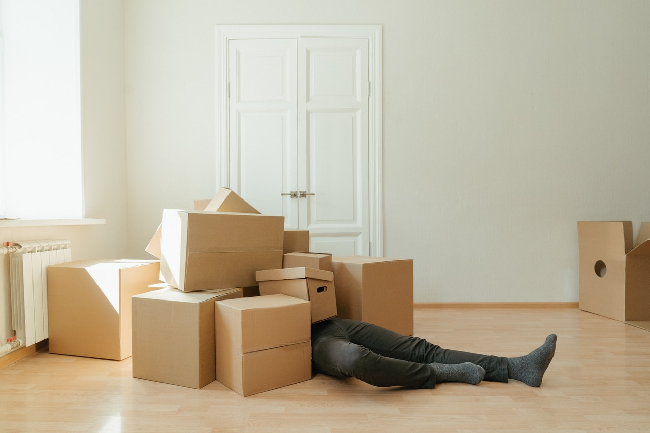 A man lying on the floor covered in carton boxes