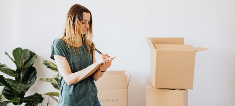 A woman writing something near boxes.