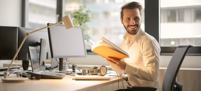 A man sitting at his desk and smiling while holding a book.