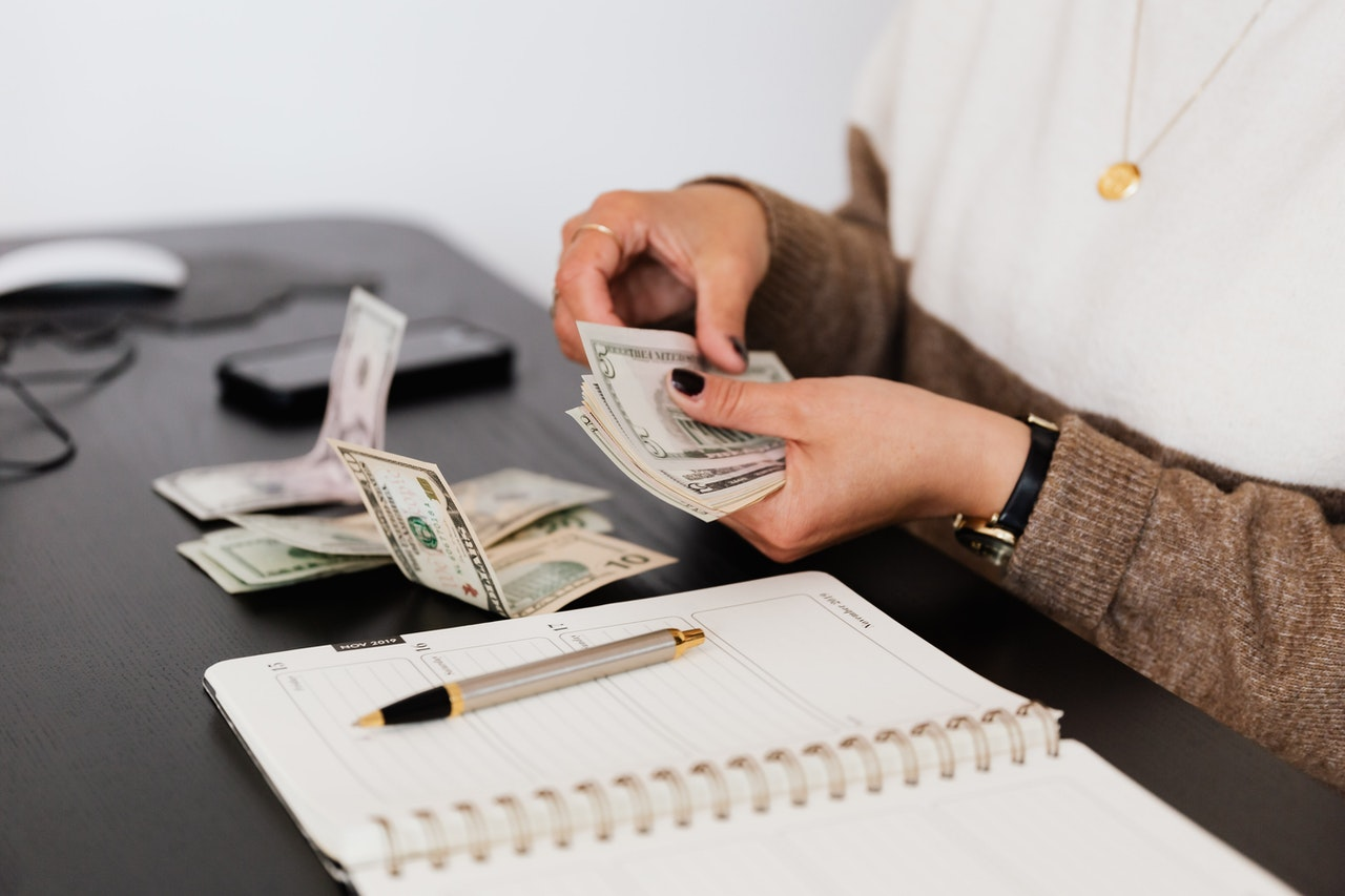 A woman counting money over a notebook, looking for ways to save money on storage expenses.