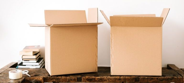 Two cardboard boxes on a wooden surface, which you can store after choosing appropriate storage units.