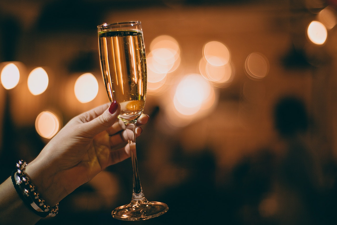 A woman holding out a glass of champagne, representing the need to prepare glass items for storage.