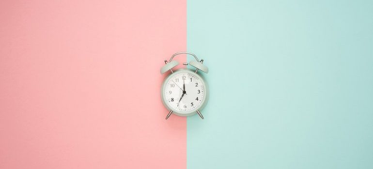 An alarm clock on a pink and blue surface,