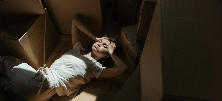 Woman lying on the ground surrounded by boxes