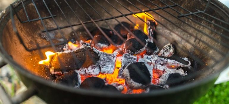 A grill with burning charcoal inside.