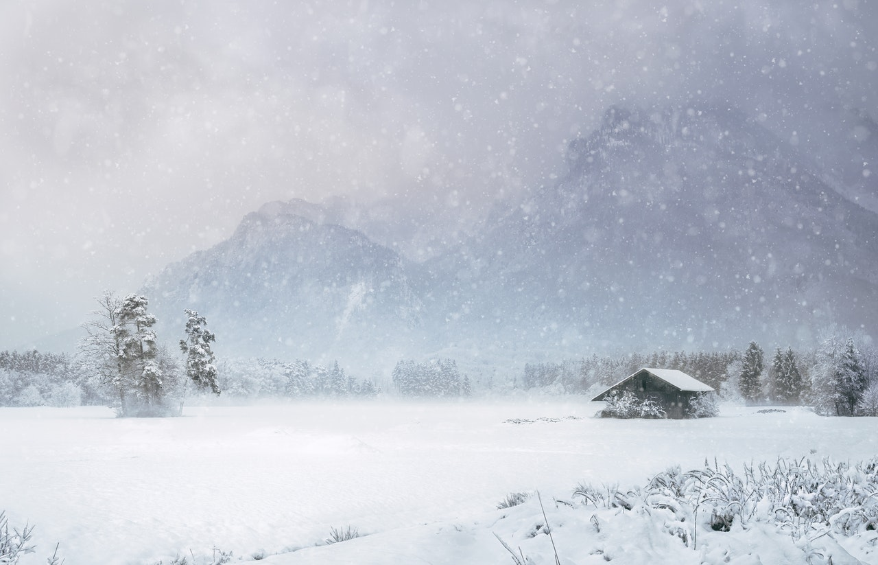 A single house in the middle of a snowy field, representing the need to prepare items for winter storage.