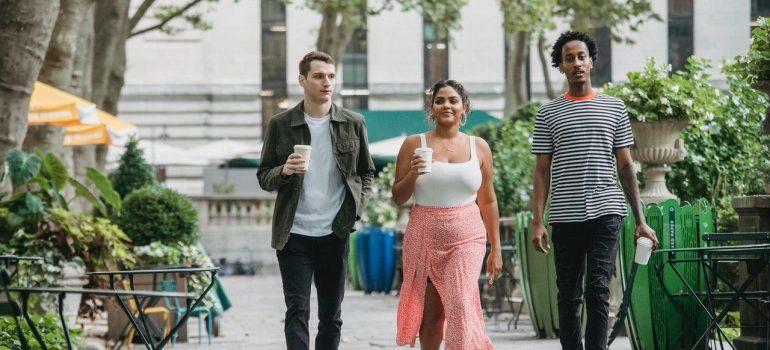 three friends walking down the street drinking coffee