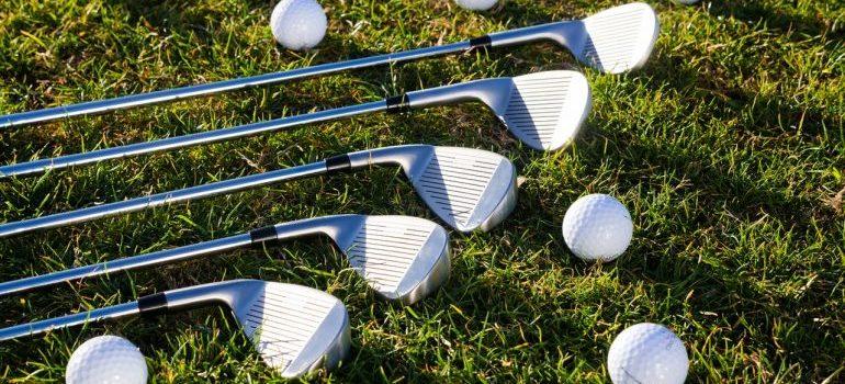 Golf balls and golf clubs on grass.