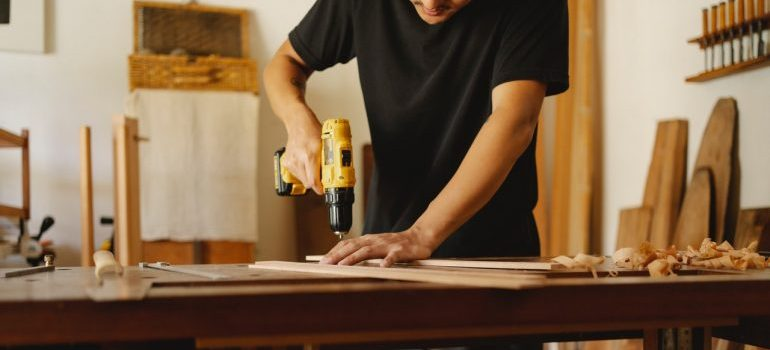 A man drilling a wooden table.