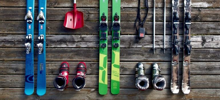 Different pairs of skis on a wooden floor.