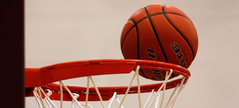 A basketball going into the hoop.