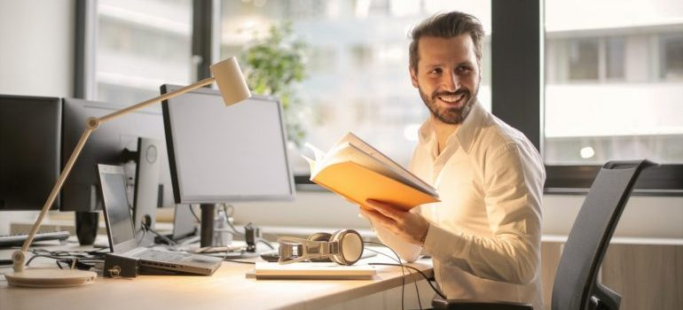 Man smiling and holding a book while sitting in his office.