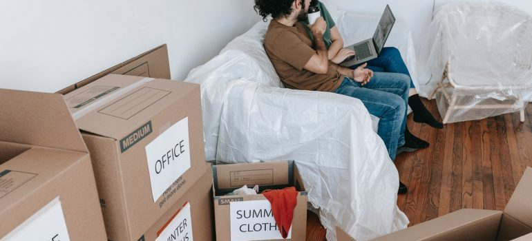 Cardboard boxes and a couple sitting on a sofa
