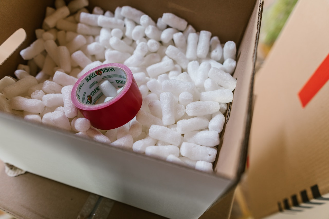 A box with packing peanuts and tape, representing signing a storage rental agreement.