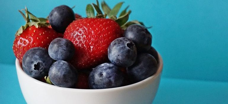A bowl of fruit against a teal background.