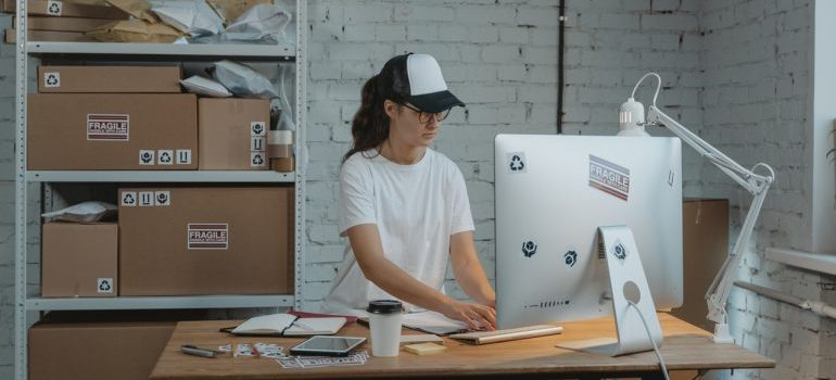Woman standing in office working on computer with moving boxes behind.