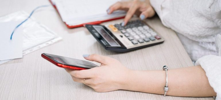 A woman looking at a phone while typing numbers into a calculator