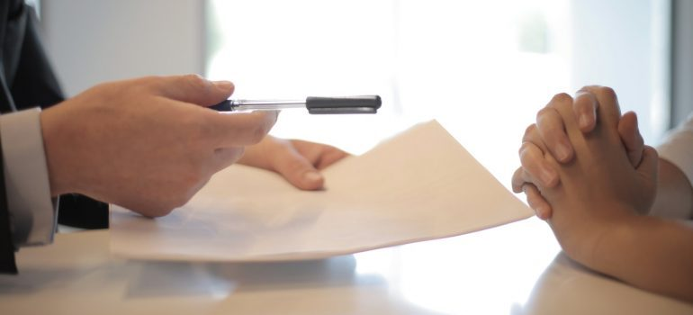 An employee handing over a contract to a client.