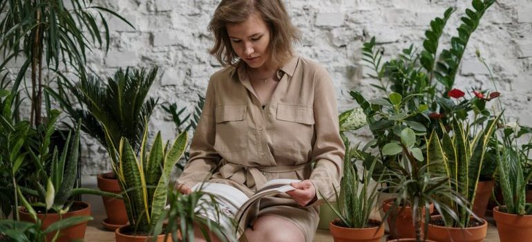 A woman reading a book about plants.