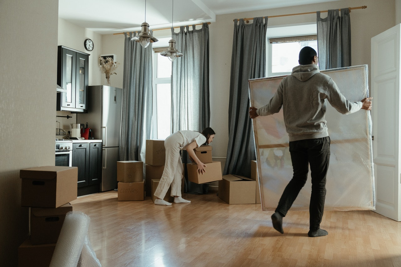 a couple moving items into the living room after they finished packing