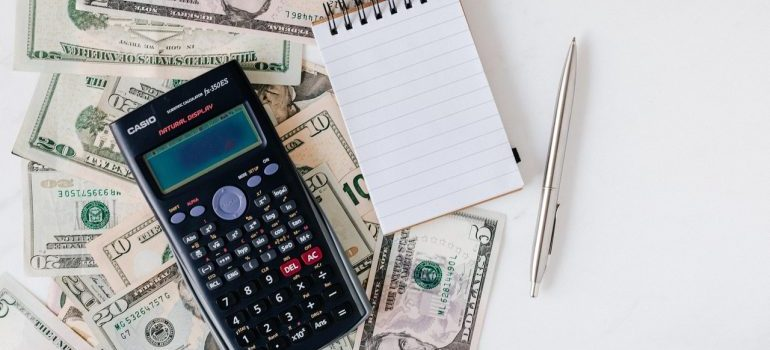 Calculator, pen, money and notes on the table.