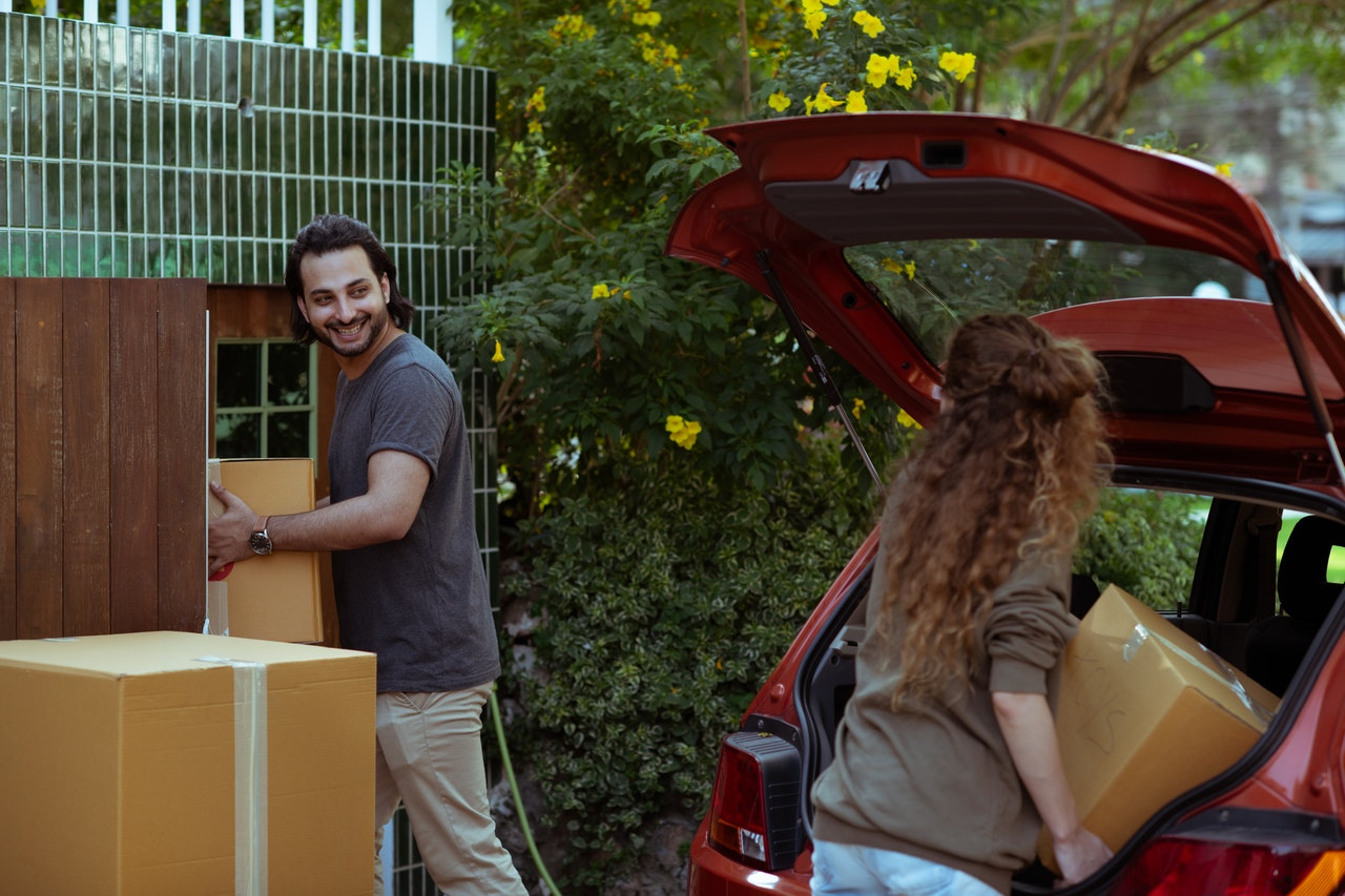 a couple moving boxes from their home to their car