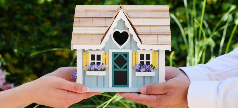 Two peoples hands holding a small wooden house.
