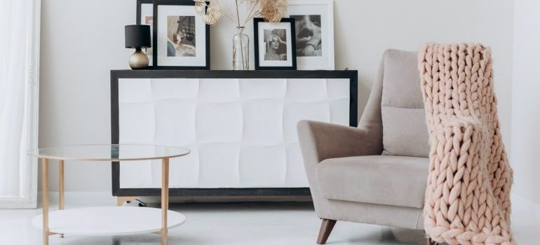 Armchair with a blanket, tea table and a shelf with pictures.