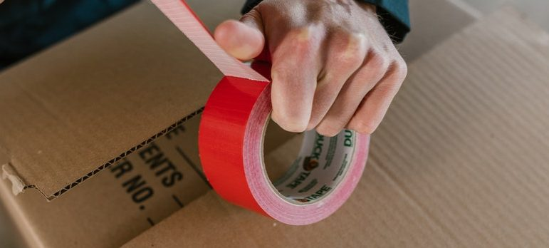 A guy using a packing tape on a box