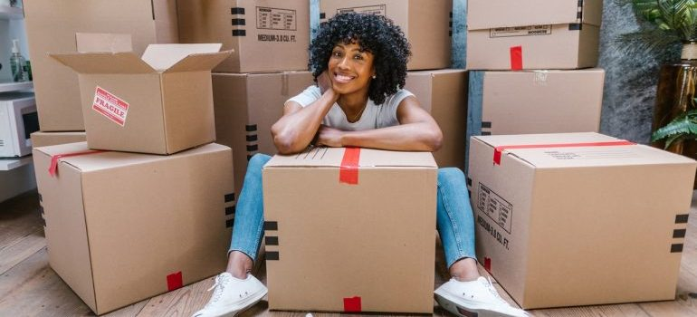 a girl with boxes, representing moving back home