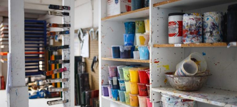 A storage filled in with paint and brushes.