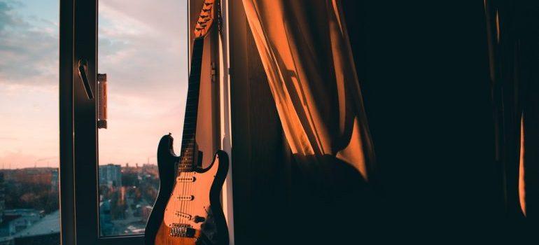A guitar next to a window.
