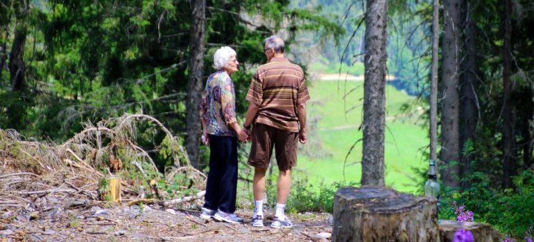 an elderly couple holding hands in nature