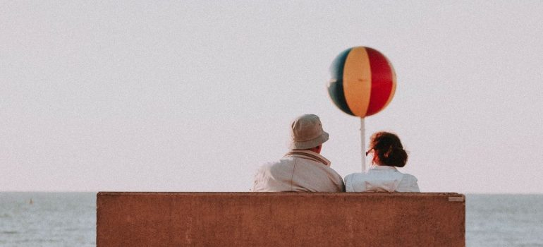 an elderly couple sitting on a bench by the beach with a balloon in their hands
